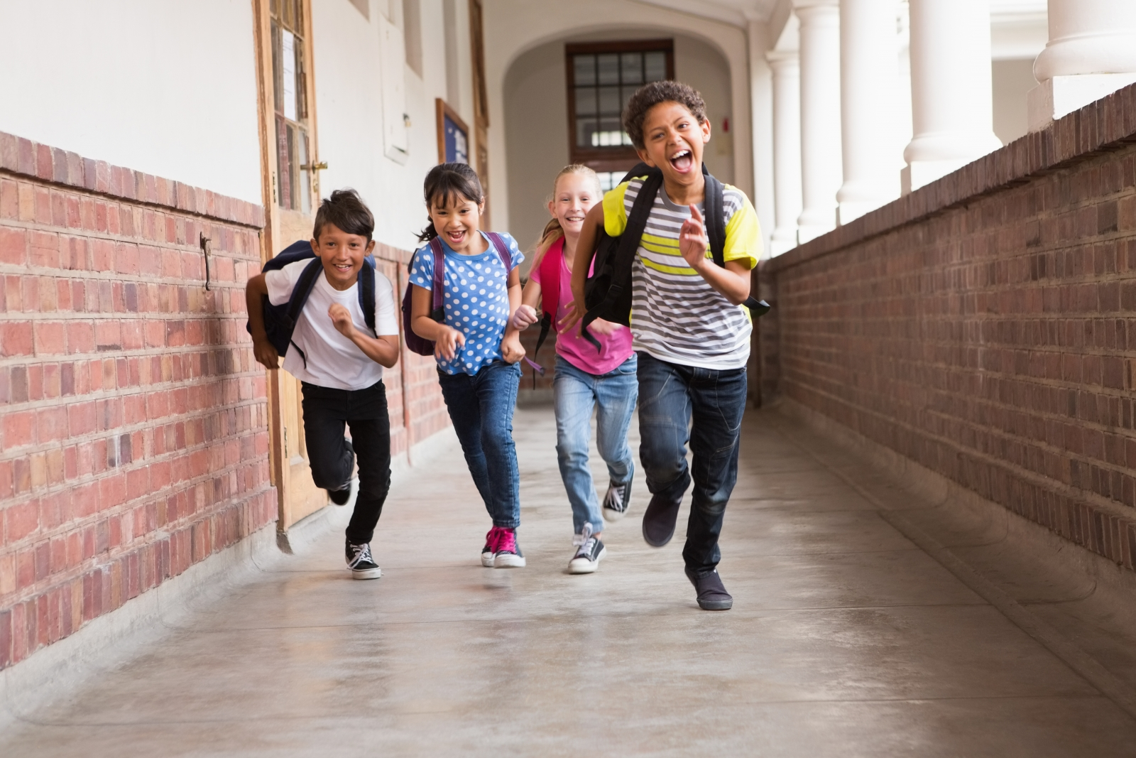 kids running towards camera down school hallway
