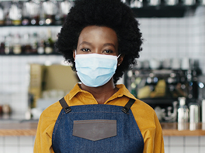 Black female staff member wearing a face mask standing in food establishment