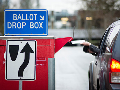 Woman dropping off ballot to secure ballot box